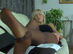 Heated blondie massaging her tasty feet right throughout her suntan hose