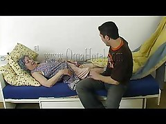 Horny couple sit next to a much older woman Heidi who`s laying on the bed. They start taking their own clothes and stripping the granny too. Old woman has a sexual toy and she wants to play with it also. She sticks the dildo in her wet cunt while the couple are squeezing or licking her saggy titties!